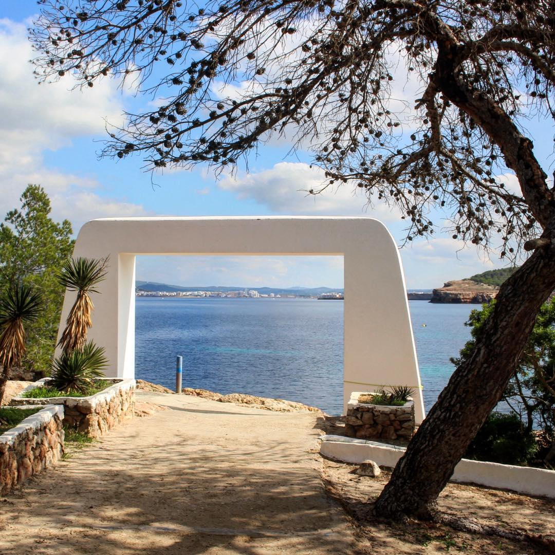 The view to San Antonio framed by a white portal at Cala Bassa Beach Club #cbbc #calabassabeachclub #calabassa #beach #beachclub #playa #sanantonio #inframe #portal #playa #spain #igersibiza #seaview #coast #westcoastibiza #ibizadiary #ibiza #ibiza2016 #cala #santantoni #ibizaplaya #instatravel, Cala Bassa - Ibiza